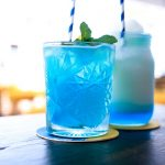 Two blue cocktailes in the glass on the table in a sunny day