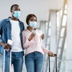 Coronavirus Travels. African American Couple Wearing Protective Medical Masks In Airport Terminal