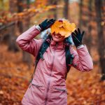 Beautiful happy blond adult woman with a smile holds autumn yellow orange leaves hiding her face with fall colored forest trees in background